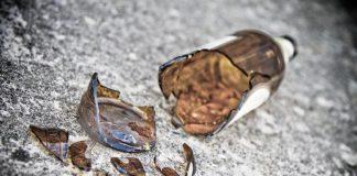 zerbrochene braune Glasflasche liegt auf dem Boden